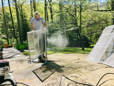 Picture of a man cleaning window screen :Pisgah Forest